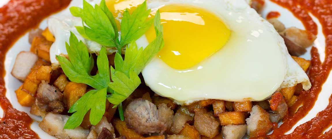 Pork Belly Sweet Potato Hash with Harissa Sauce and a Sunny Side Up Egg